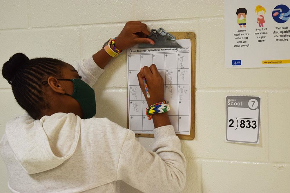 student leans against wall with clipboard, working on a math problem
