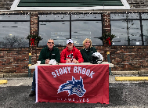 Franco Milano sits outside Kobacher's with family behind a table with Stony Brook sign