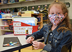 masked student sits in classroom in front of project