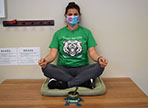 Rebecca Archer sits cross legged with a meditation bowl