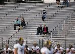 Fans sitting in bleachers spread apart and wearing masks