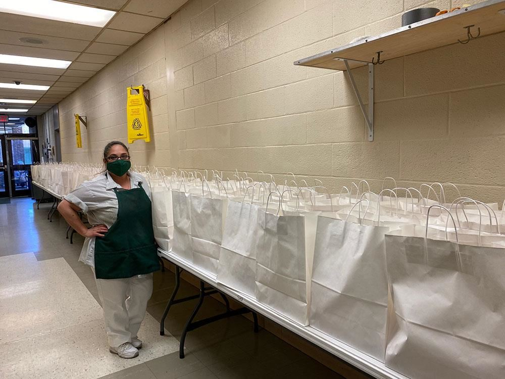staff member stands next to organized meal bags