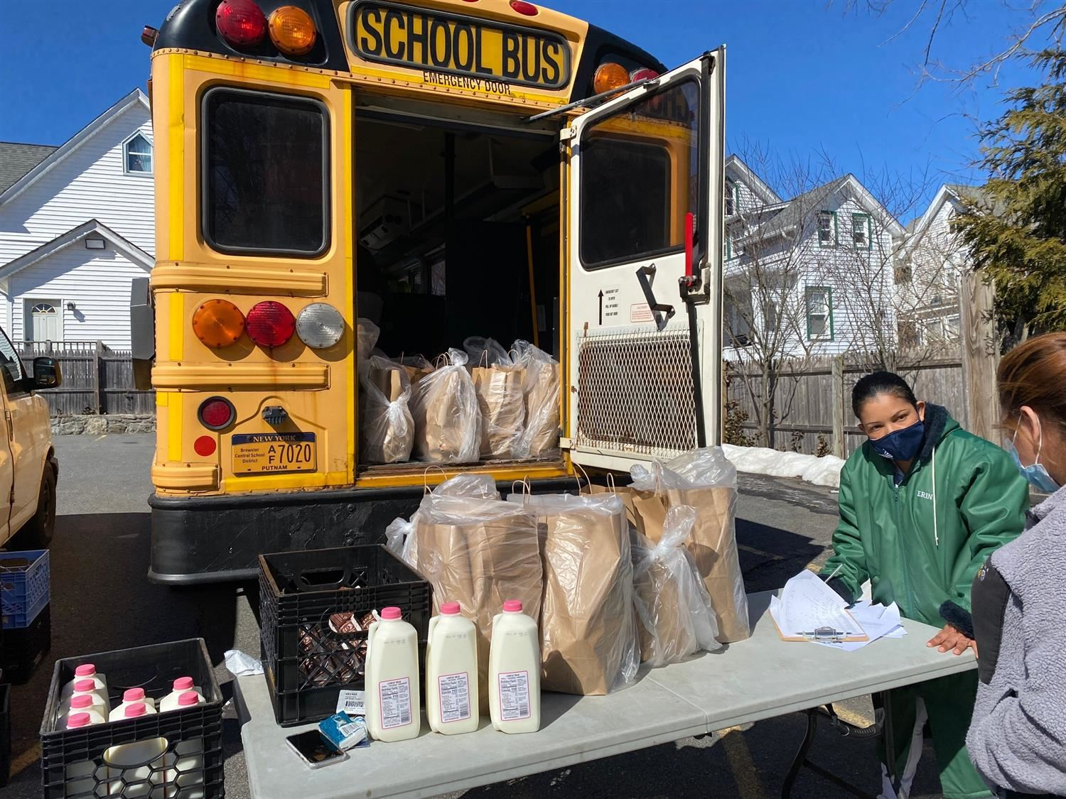 a table of food for distribution is set up in front of a school bus
