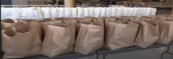 Shopping bags filled with food lined up on tables